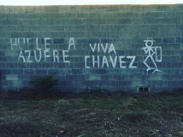 """A message to the US military painted outside on the cement wall that surrounds the US military base """"Palmerola""""in #Honduras. """"It smells like sulfur. Long live Chavez"""" (& the symbol painted in public areas all over the country that signifies that Hondurans don't want to migrate & leave their country, undocumented, for the US)"""