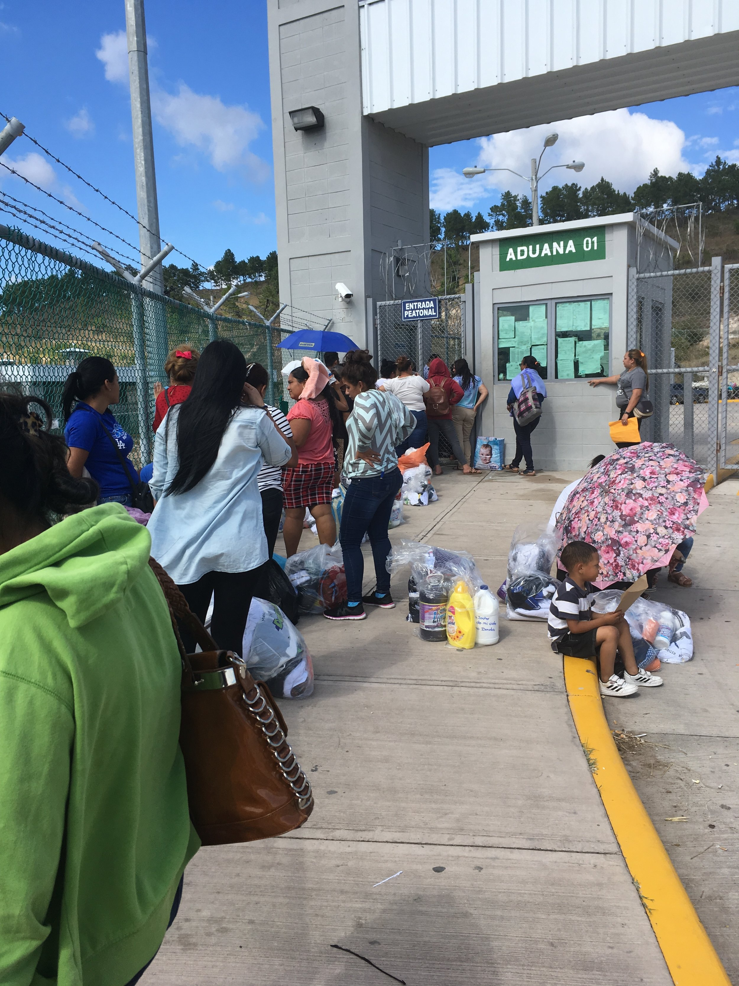 Waiting in a long line ups out in the hot sun in 'Customs One' in La Tolva in order to drop off clothes and hygiene kits for Edwin and Raul