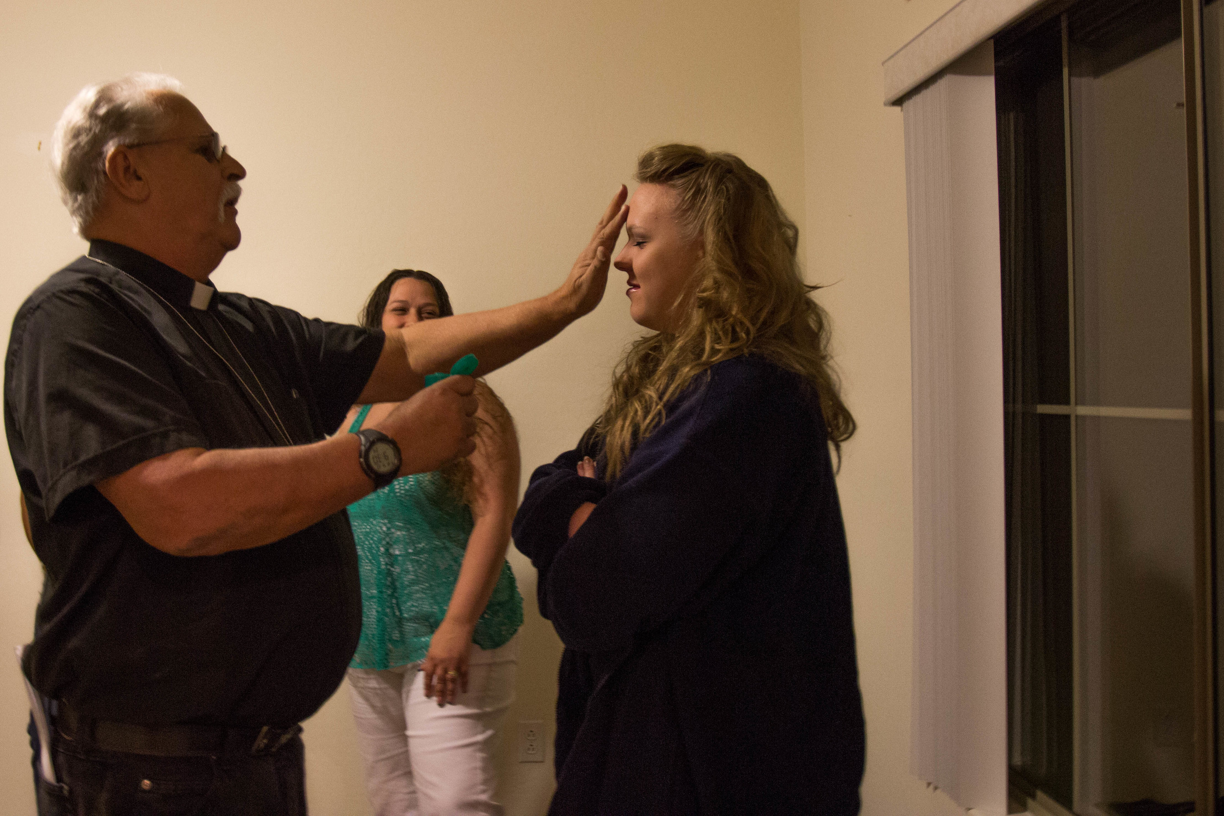 Ordained Minister and COPS crew investigator Paul Lovegrove applies holy water to investigators' foreheads before the investigation at the Superstition Mountain residence begins Friday night. (Photo by Gretchen Burnton)