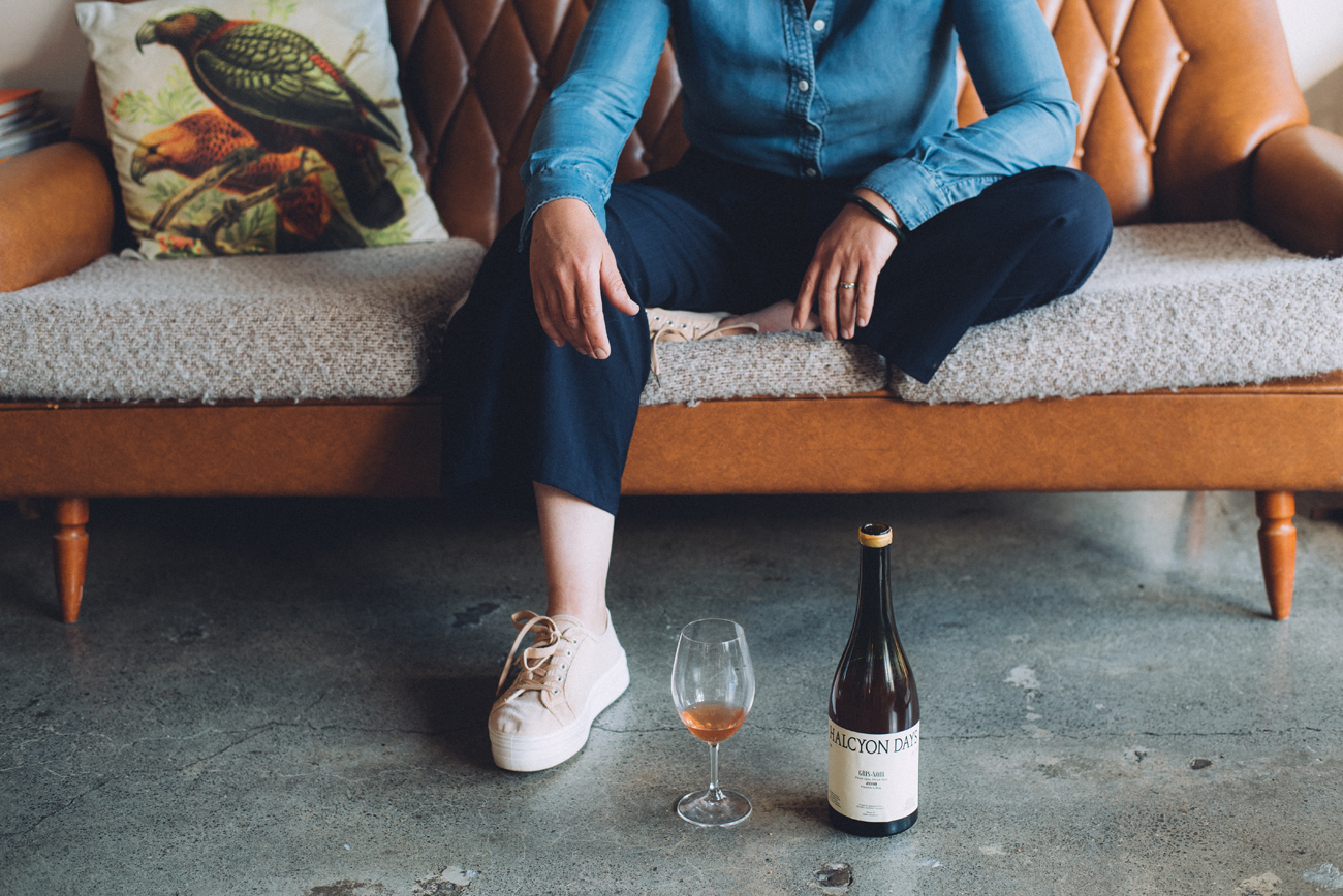 Lifestyle shot of a glass of Halcyon Days wine next to the bottle with person on a sofa