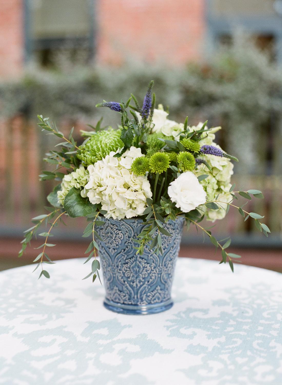 White and green flower arrangement in antique blue vase