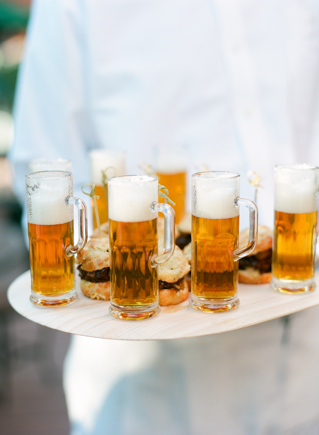 Passing tray of mini beer mugs and sliders