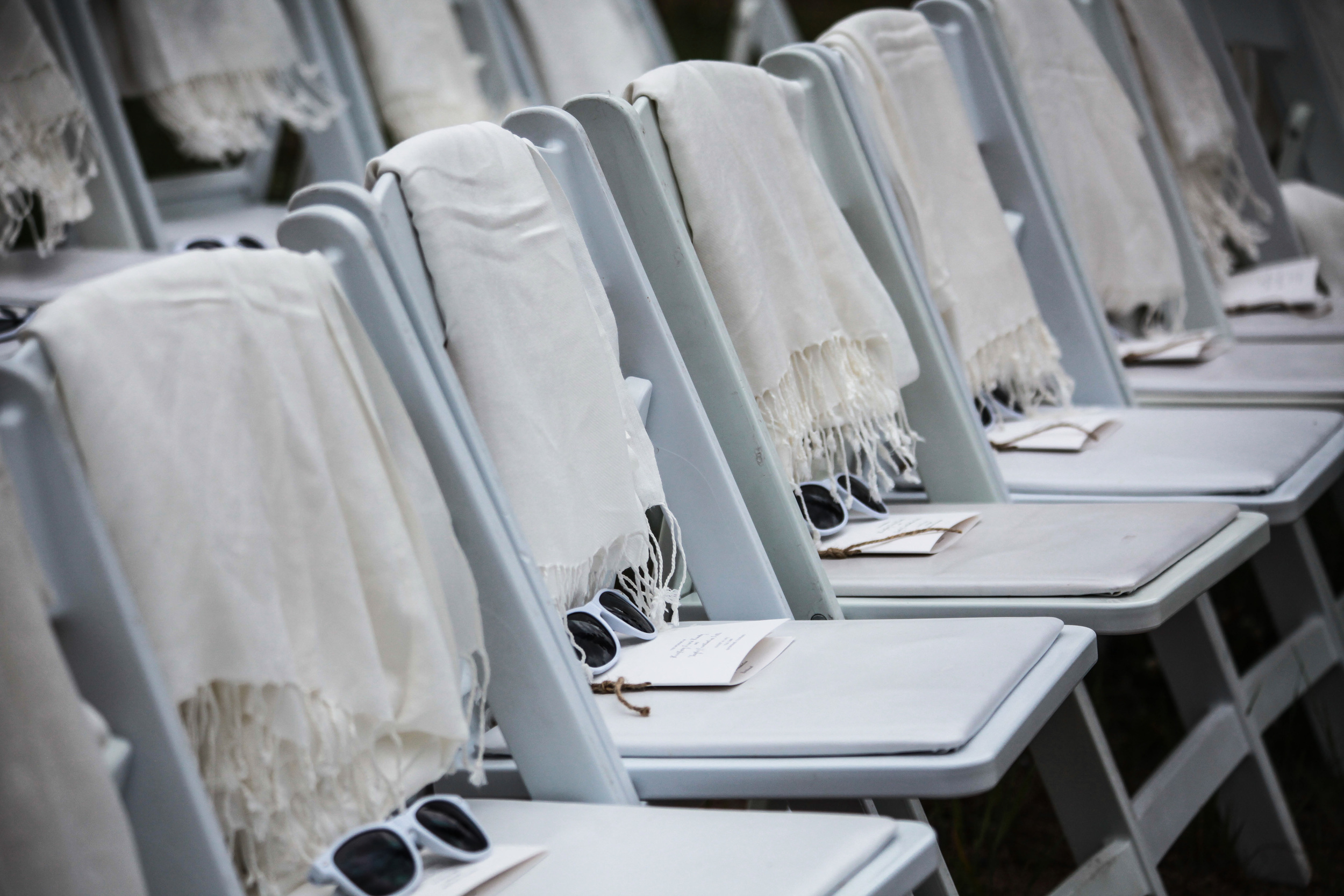 White Ceremony Chairs with Shawls, Sunglasses and Programs