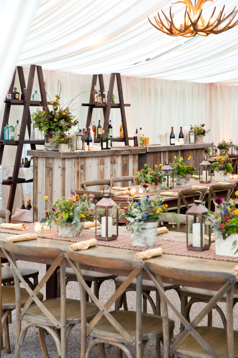 Farm tables with rustic flower arrangements and lanterns