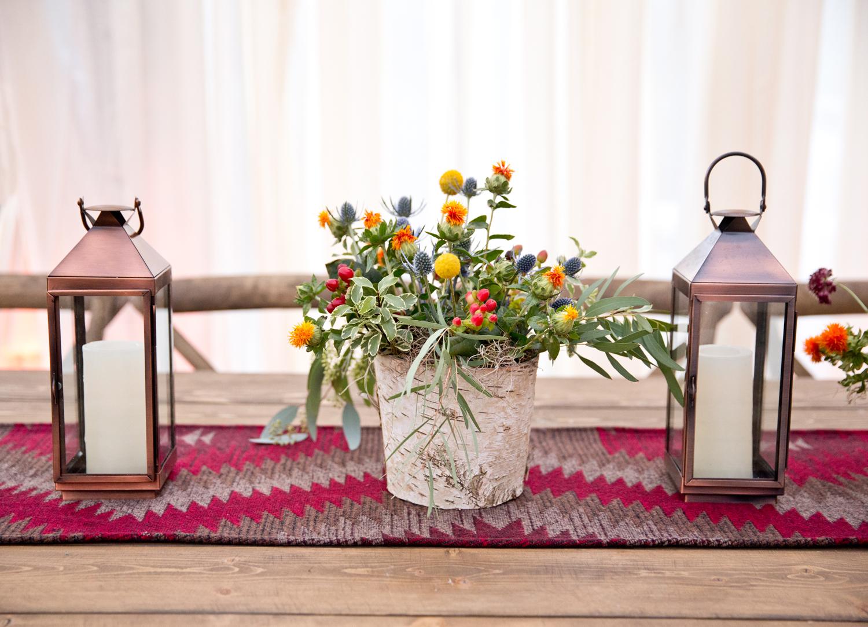 Rustic flower arrangement between copper lanterns
