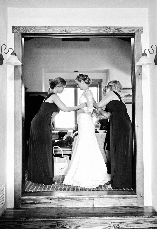 Bridesmaids helping bride into her dress