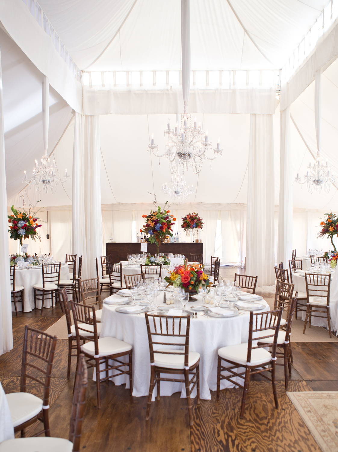 Inside reception dinner tent with white tables, farm chairs and fall centerpieces