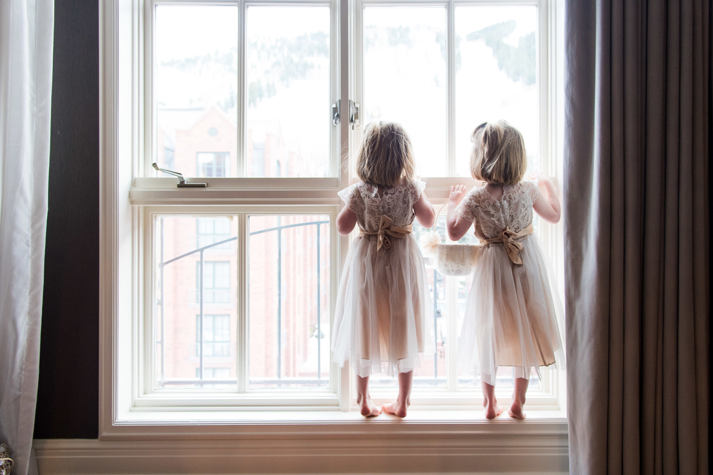 Two Flower Girls Peering Out Window