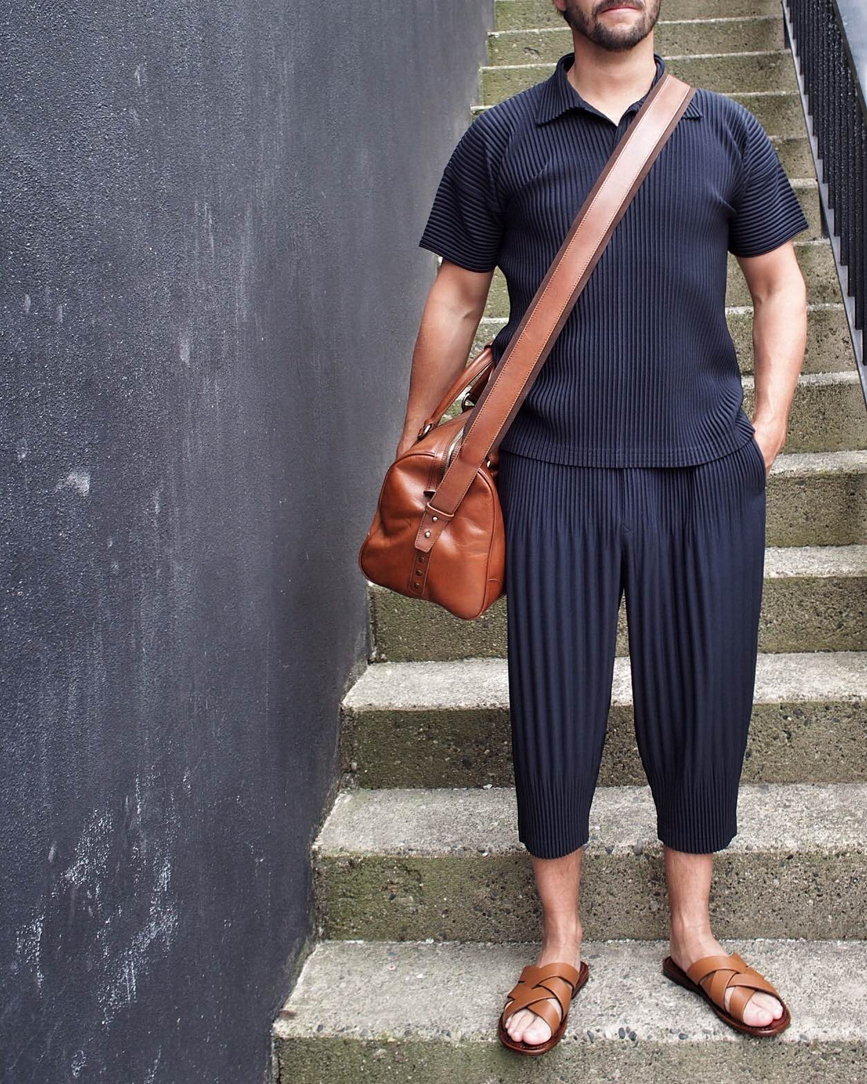Homme Plisse cropped trousers and polo - with Maison Margiela bag and Pete Sorensen slides