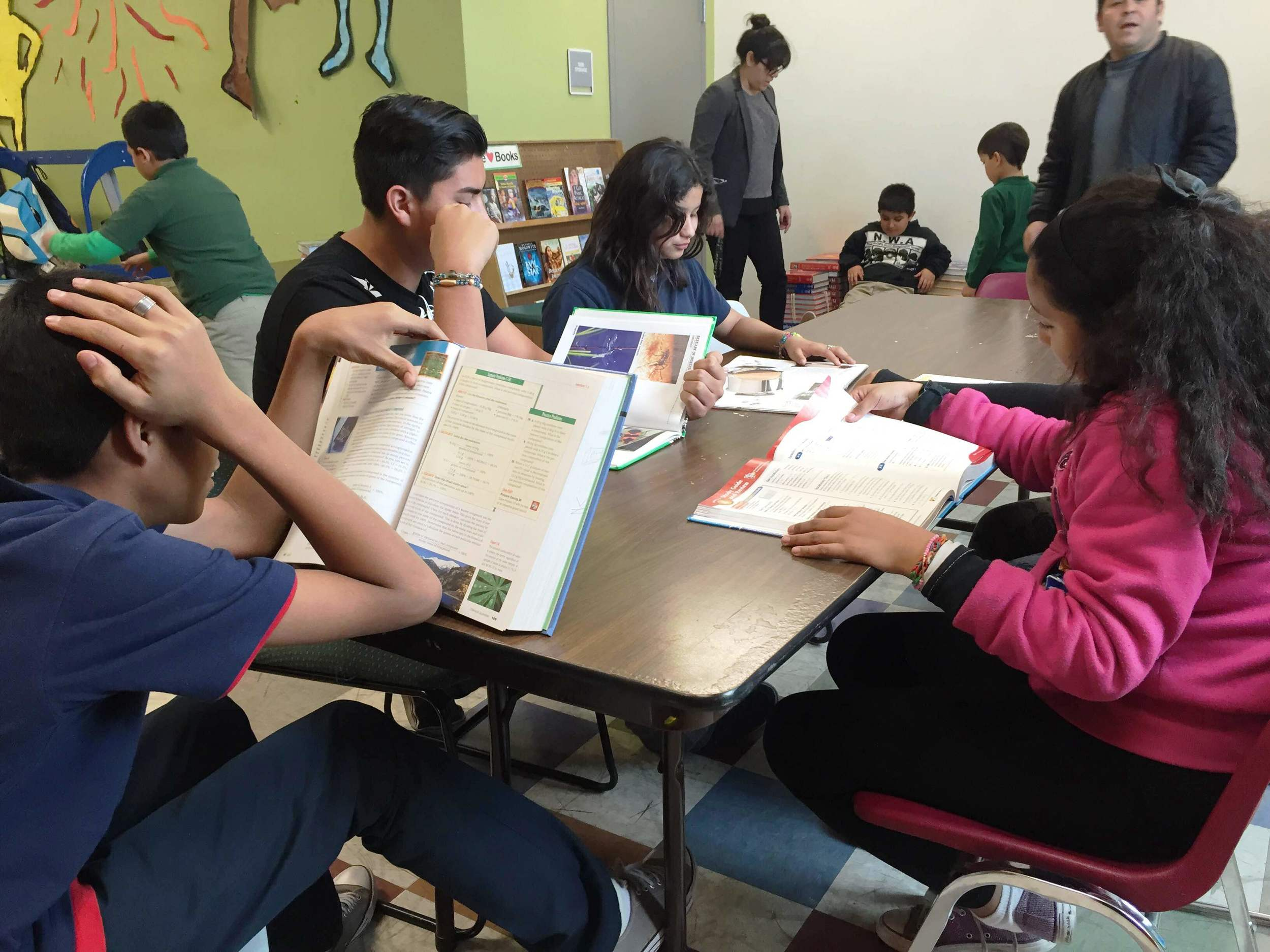 Teens in After-School Enrichment studying homework assignments.
