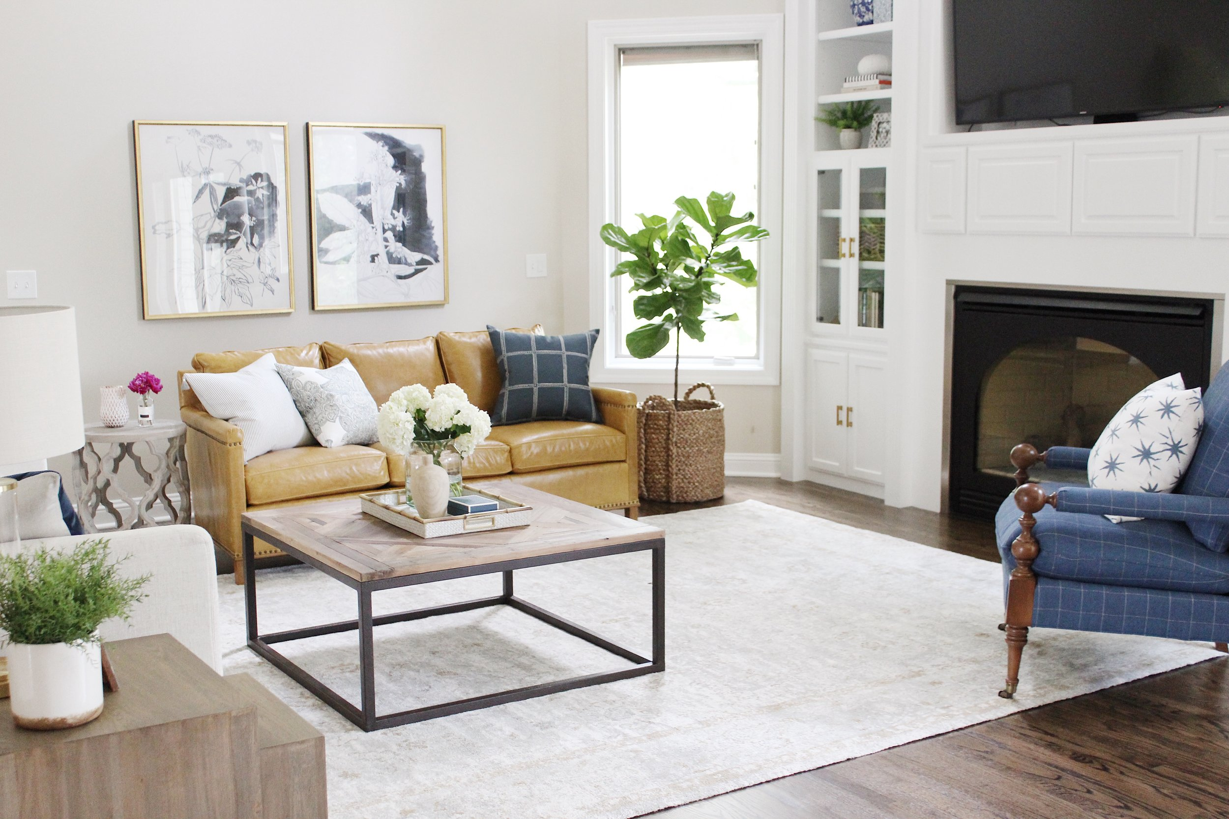 AFTER...The space was transformed into a  bright,classic family room  with broad appeal. The flooring was updated, while fresh paint on the walls, trim, built-ins and staircase improved the home's aesthetic-- and market-- value.