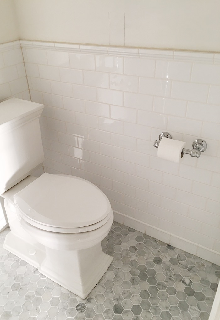 One Room Challenge- Powder Room New Build by Laura Design Co. - White Subway Tile with contrasting off-white grout, Kohler Memoirs toilet & RH Lugarno Tissue Holder