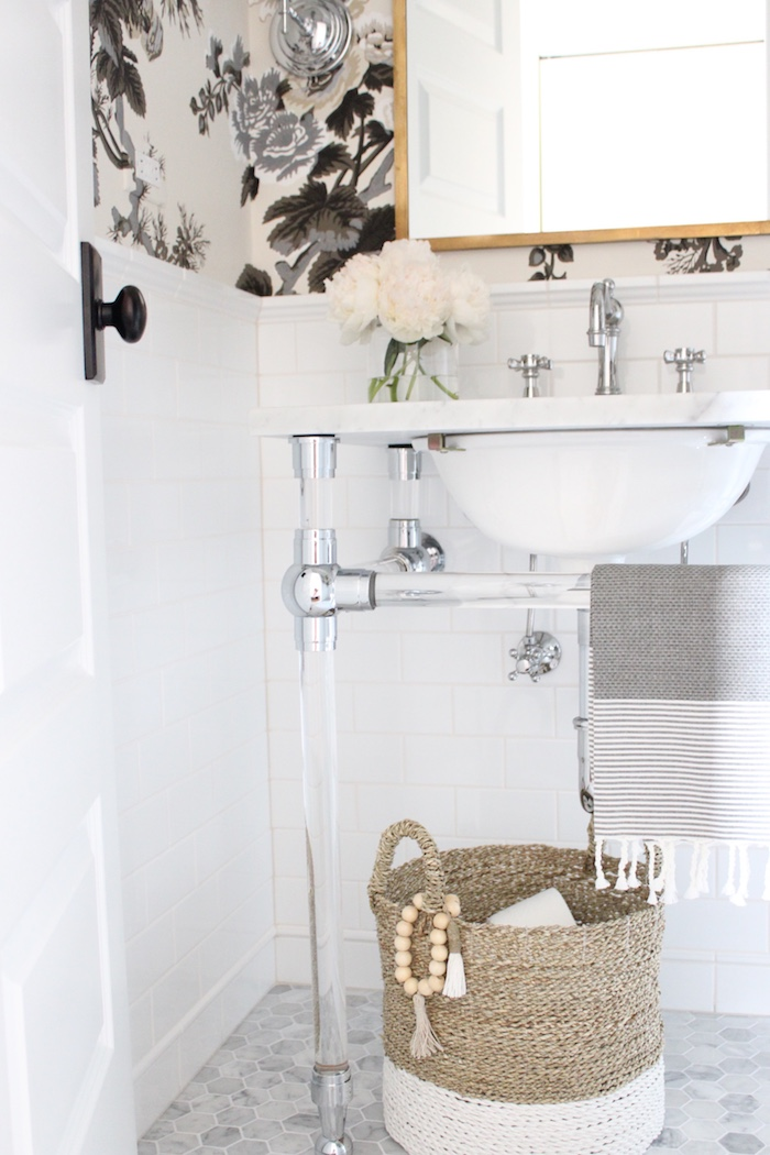 "RH Gramercy glass console sink, 2"" marble hex floor tile, white subway tile walls, vintage faucet, Moroccan mirror, Schumacher Hollyhock Pyne Charcoal wallpaper"