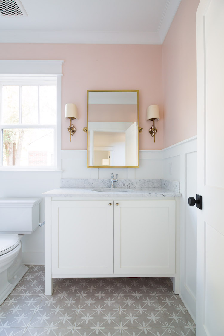Powder Room Design by Laura Design Co., Paint is Farrow & Ball Pink Ground, Floor Tile is by Laura Ashley for The Tile Shop, Carrara Marble Countertop, Chantilly Lace Vanity Paint by Benjamin Moore. Sconces are Visual Comfort & Mirror is Pottery Barn