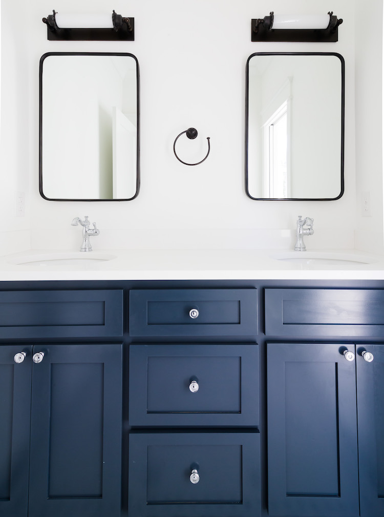 Benjamin Moore Blue Note Vanity- Mirrors by Rejuvenation, Sconces by RH - Guest Bathroom Design by Laura Design Co.