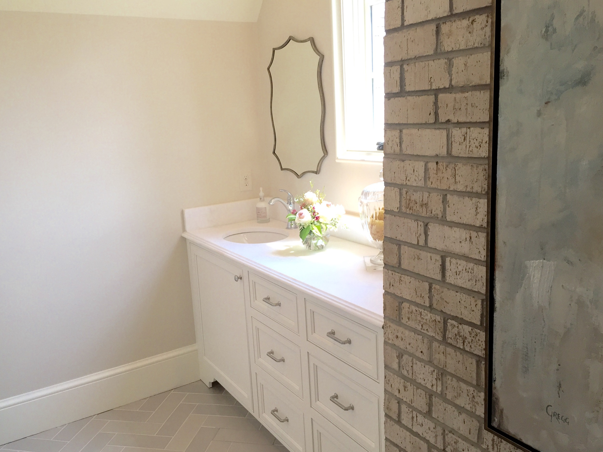 Each house had a touch of exposed brick. This bathroom paired herringbone tile floors with a stained brick for an elegant and inviting retreat.