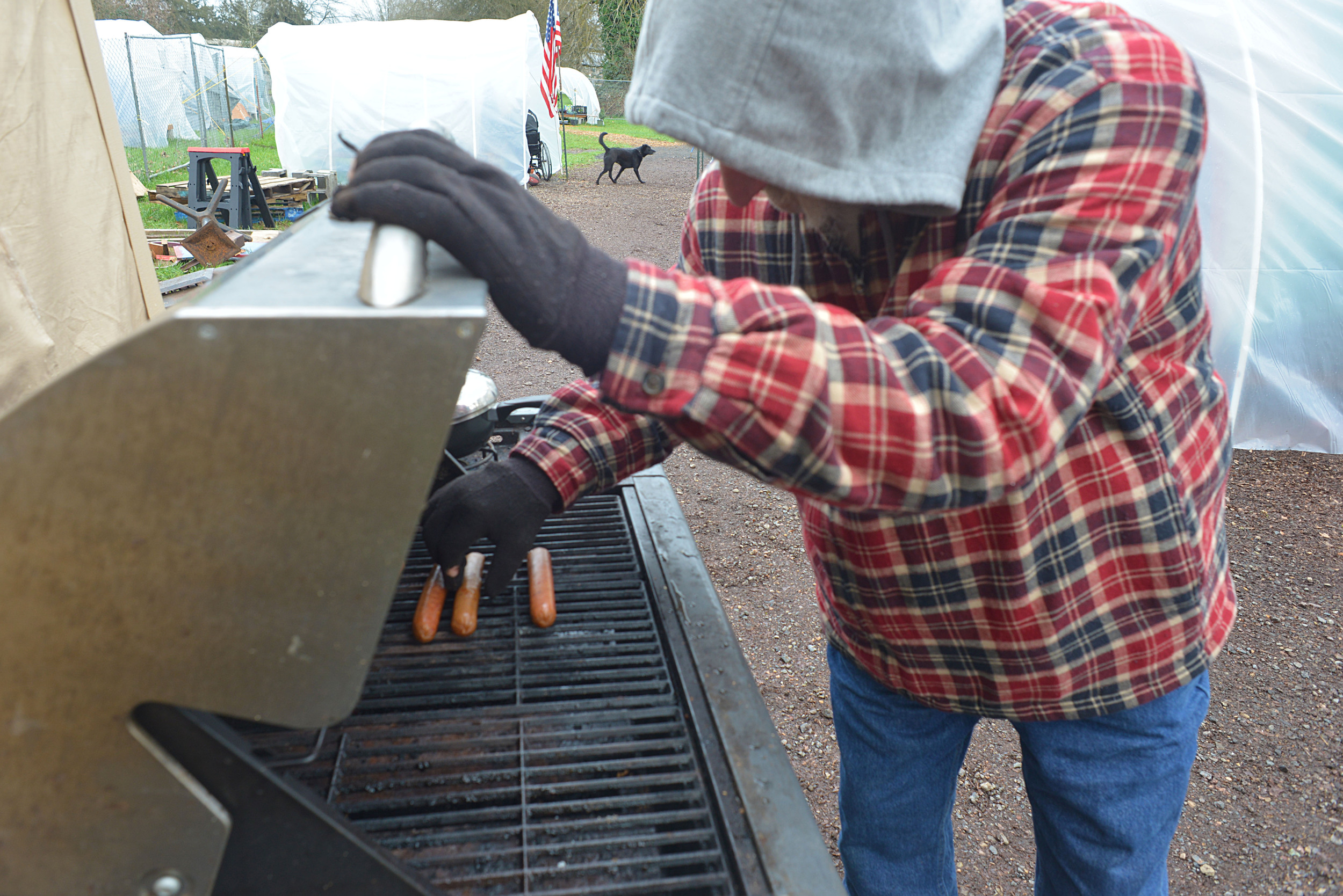 Eugene, Ore. - Mike Myers, the site manager at NHS, is cooking lunch on the propane gas grill donated to the camp by larger community. By: Debra Josephson