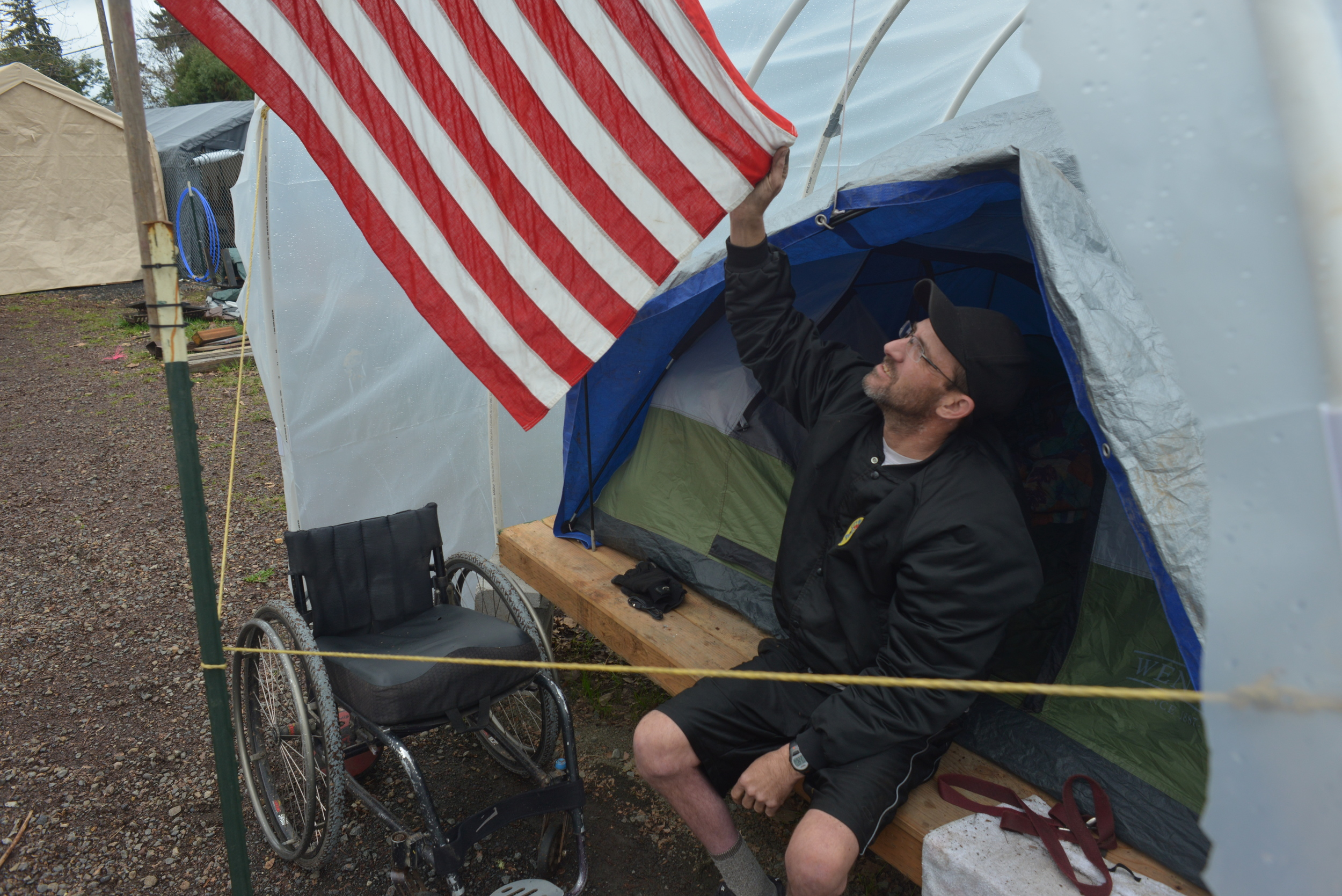 """Eugene, ORE - """"Medicine Man"""" Eric holds the American flag at his conestega housing. He says he is grateful for the opportunity to live at Nightingale Health Sanctuary. Photo by: Debra Josephson"""