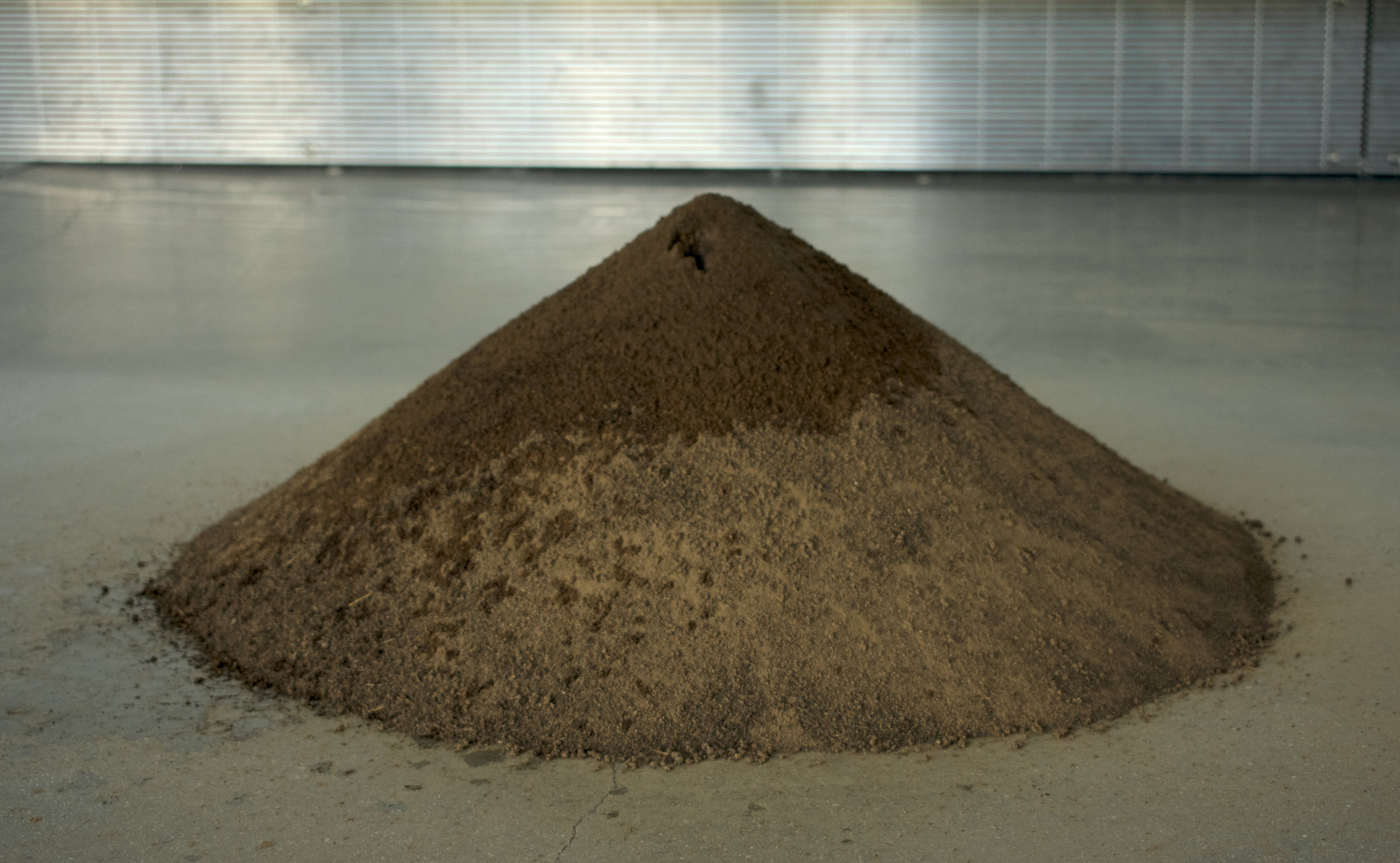 in the ebb and flow of    Sifted earth, terracotta vessel, water, and cotton cloth   Dimensions variable  2018