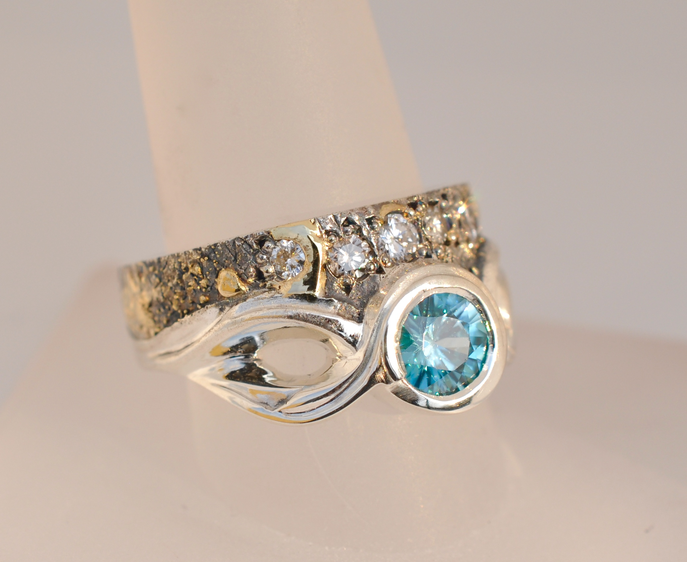 A 1.25 carat Blue Zircon is the center of attention with compliments of .45 cttw. of round brilliant diamonds, making this sculpted fusion ring a statement piece for those of a particular fashion persuasion.