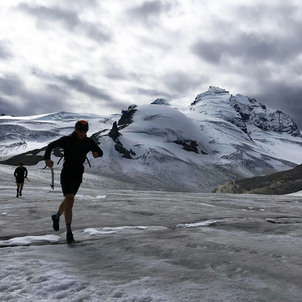 Kris and I running along a glacier with the Garibaldi Massif in the background. These storm clouds were following us all day. Photo: Eric Carter