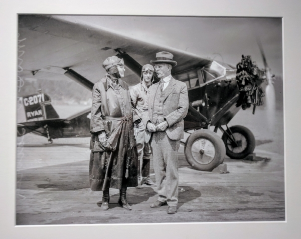 """Mrs. D.W. Barnes of Portland celebrated her 90th birthday on June 27, 1928 by taking her first ride in an airplane. Her son E.L. Barnes (possibly the man on the left) accompanied her in a Ryan monoplane flown by pilot Gordon Mounce (possibly the man in the background). More than two dozen family members and friends turned out to watch. Mrs. Barnes was an avid follower of aviation news, the Journal reported in a brief article, and had been planning the flight for quite a while. At the end of it, she ""landed breathless and pleased,"" the Journal reported."""