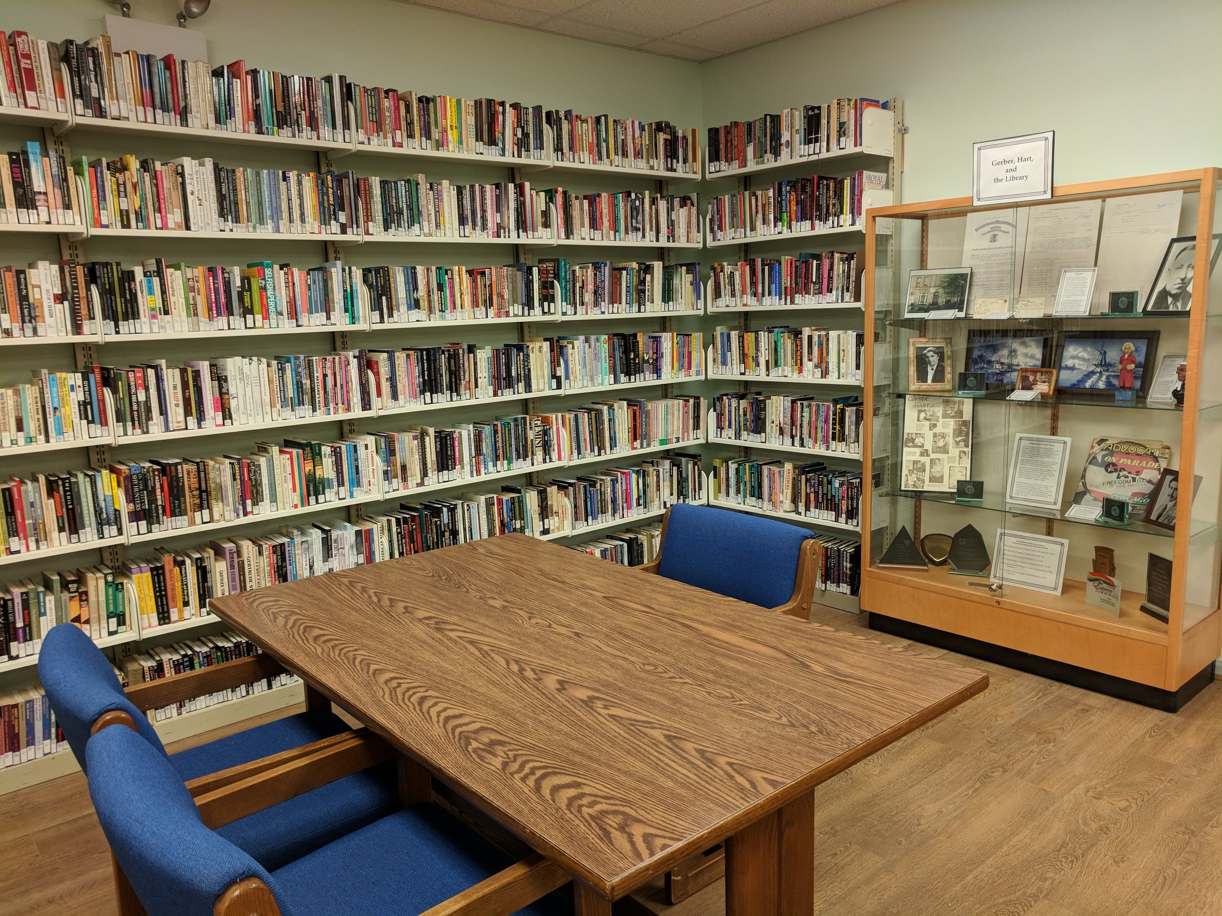 Reading room with tables for researchers to look at archival collections, exhibition cases featuring archival and special collections, and circulating library collections