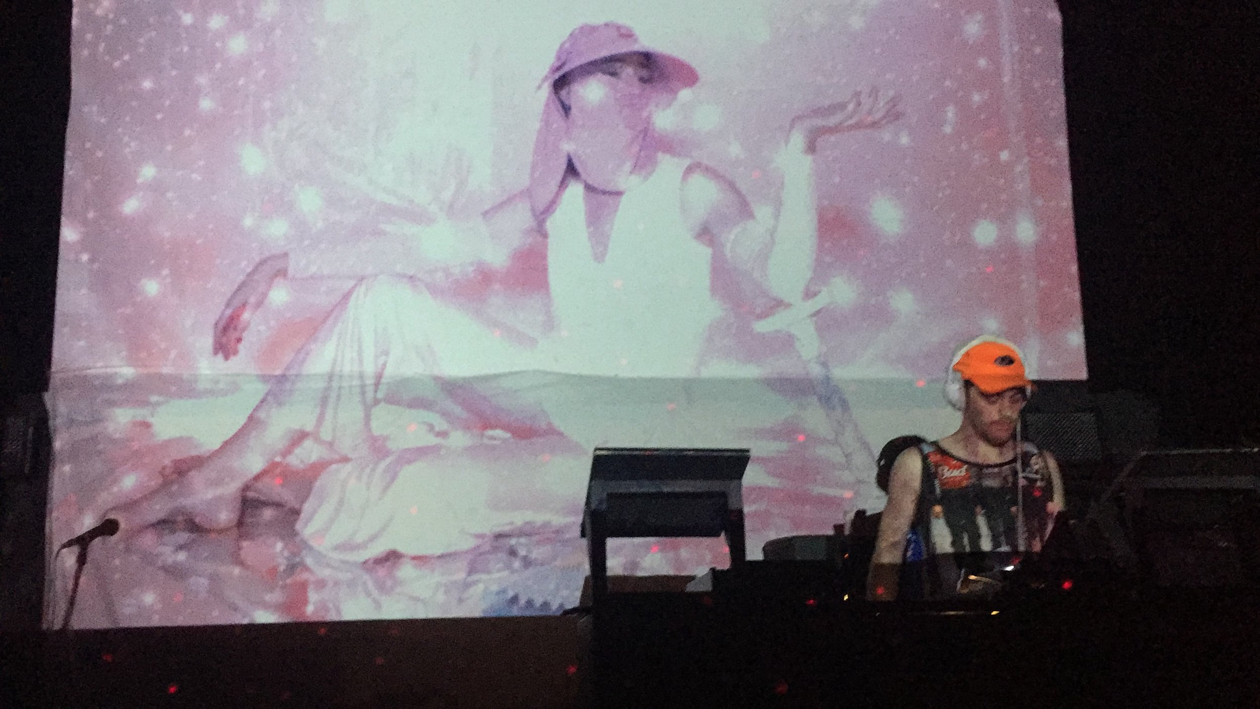 Virgo original footage being projected larger than life behind JX CANNON