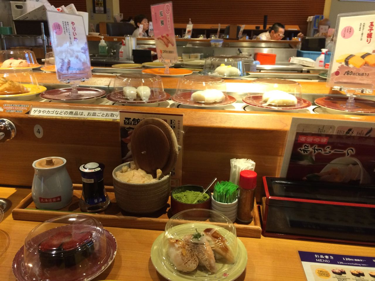 Kaitenzushi (conveyor-belt sushi) near the station.  Note the cup of matcha sitting in the row of condiments between the gari ginger and wasabi.