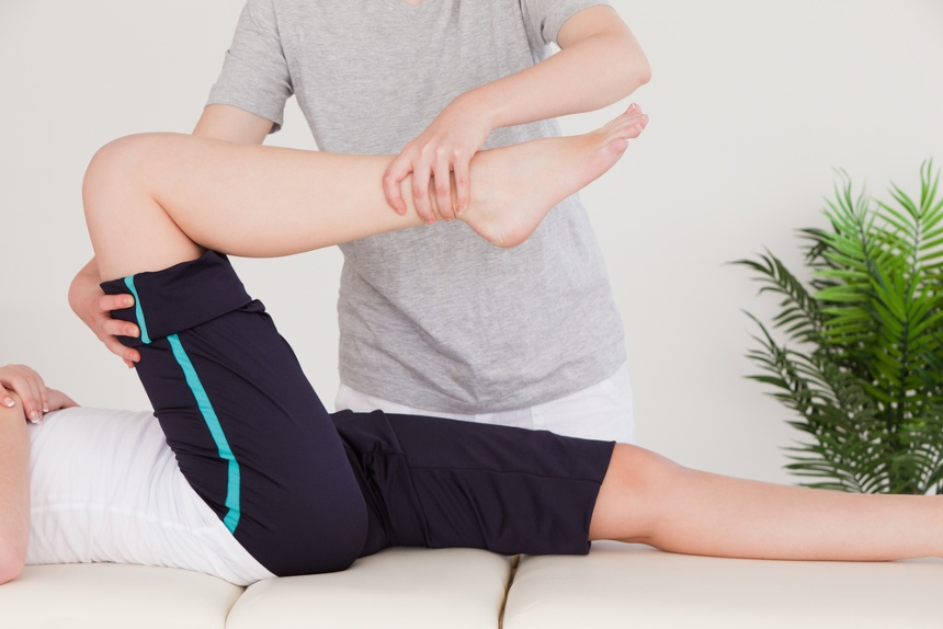 Masseuse stretching the right leg of a young woman.jpeg