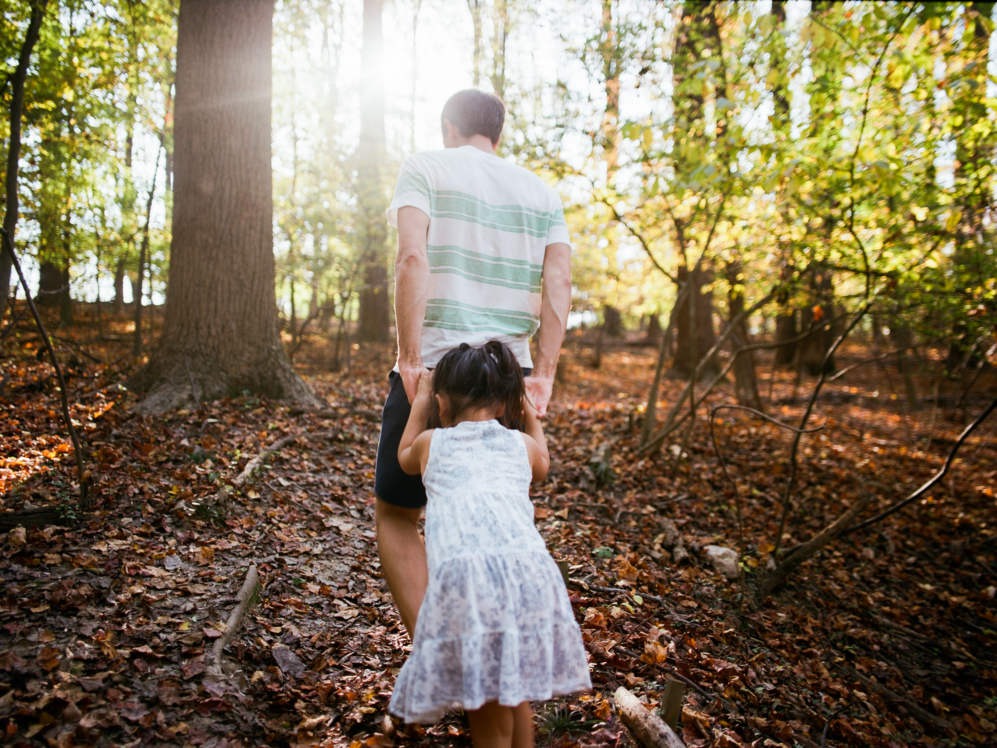 Dad and daughter hike through woods during Ventura Family Photography session