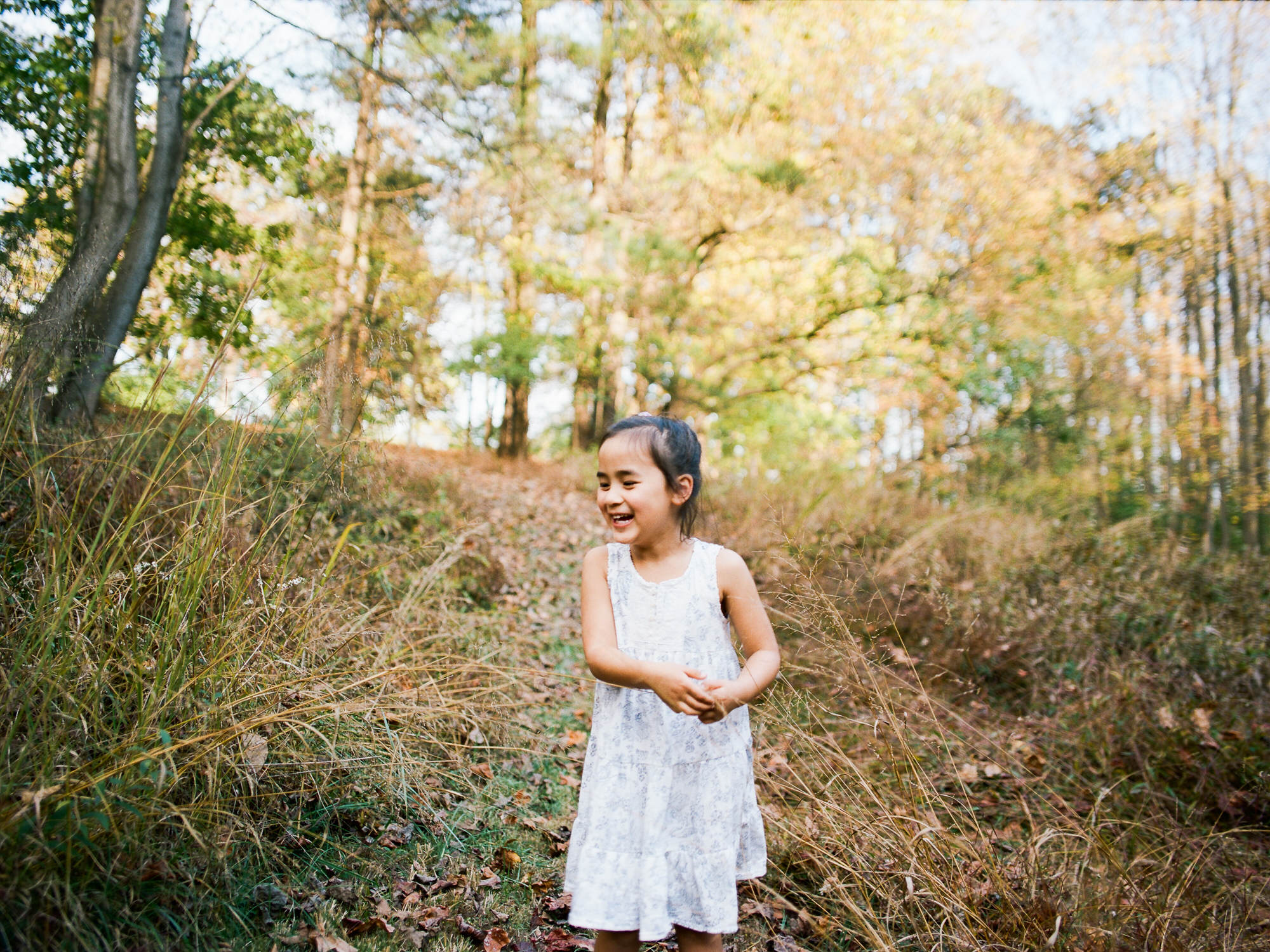 Girl laughs in forest during Ventura Family Photography Session