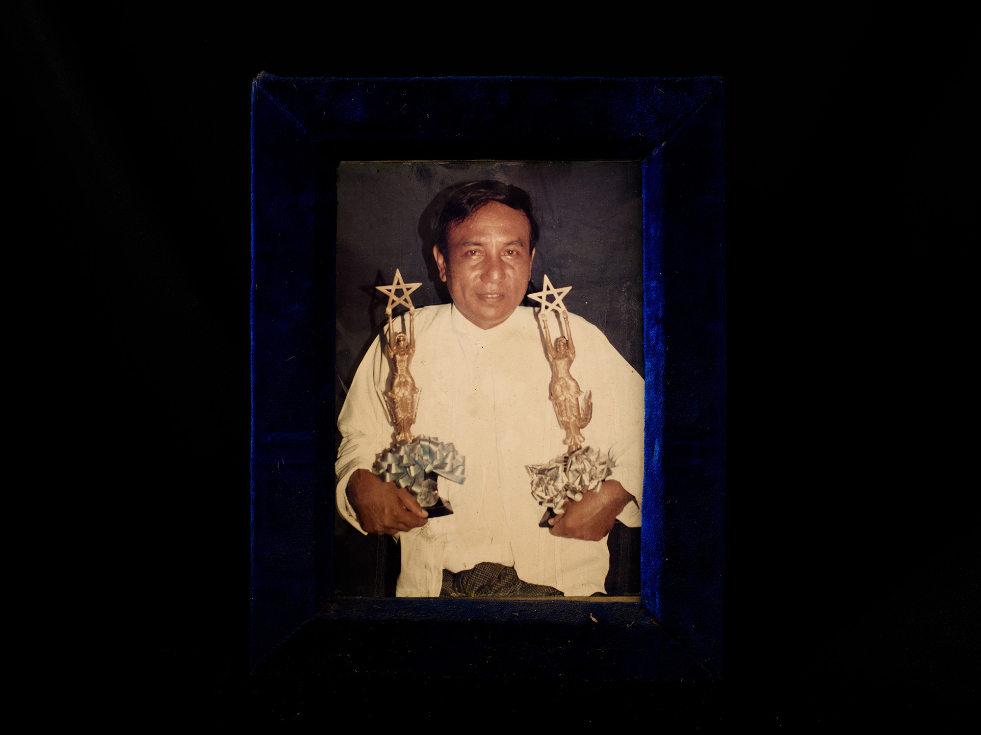 A framed photograph of cinematographer Than Nyunt holding his Burmese Academy Award trophies. Than Nyunt won praise for such films as  Myit Tot Ei Maryar  (Mystery Of The River) and  Nya Min Thar  (Nightwalker).