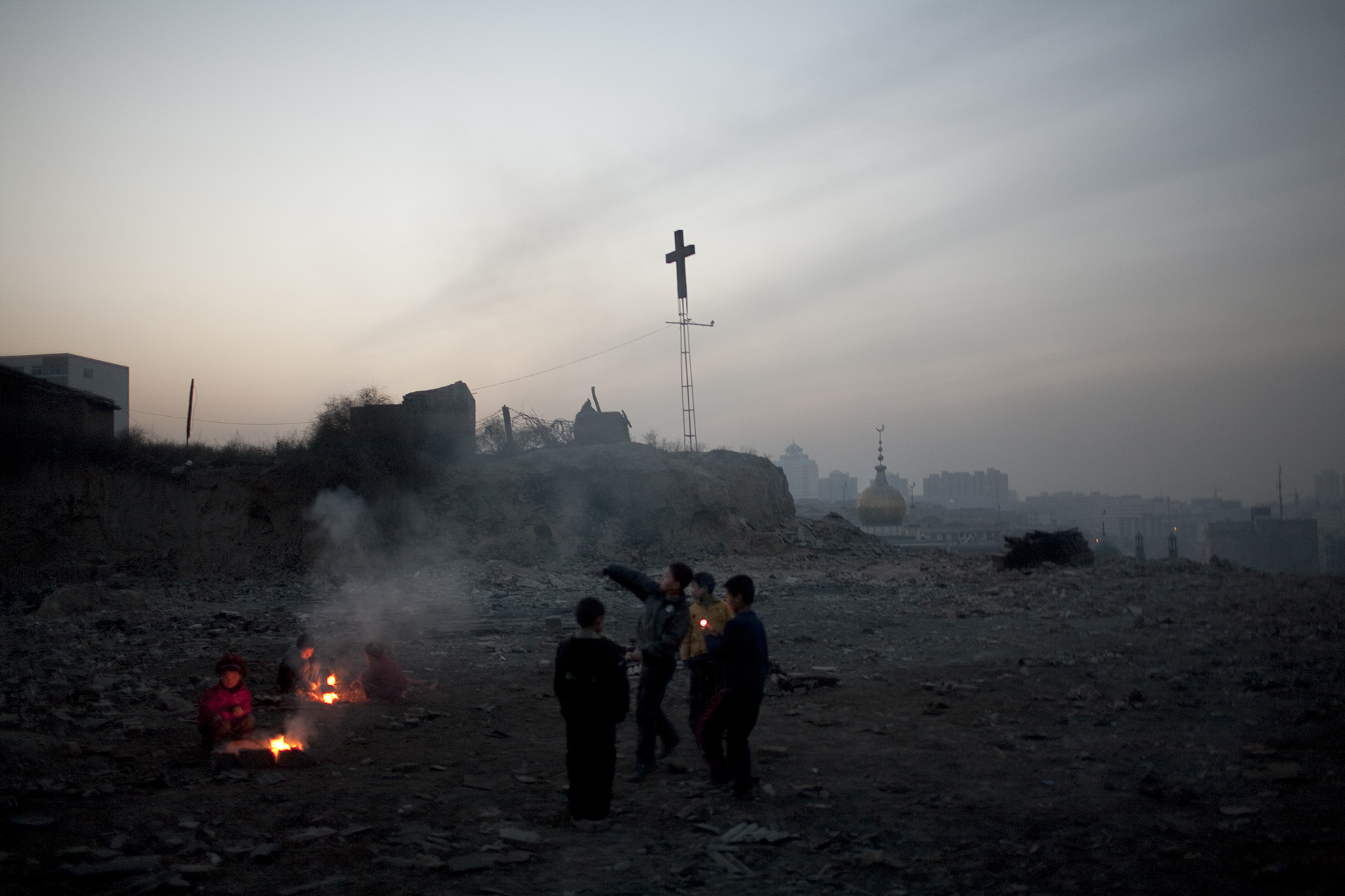 Children play with fireworks on a wasteland.
