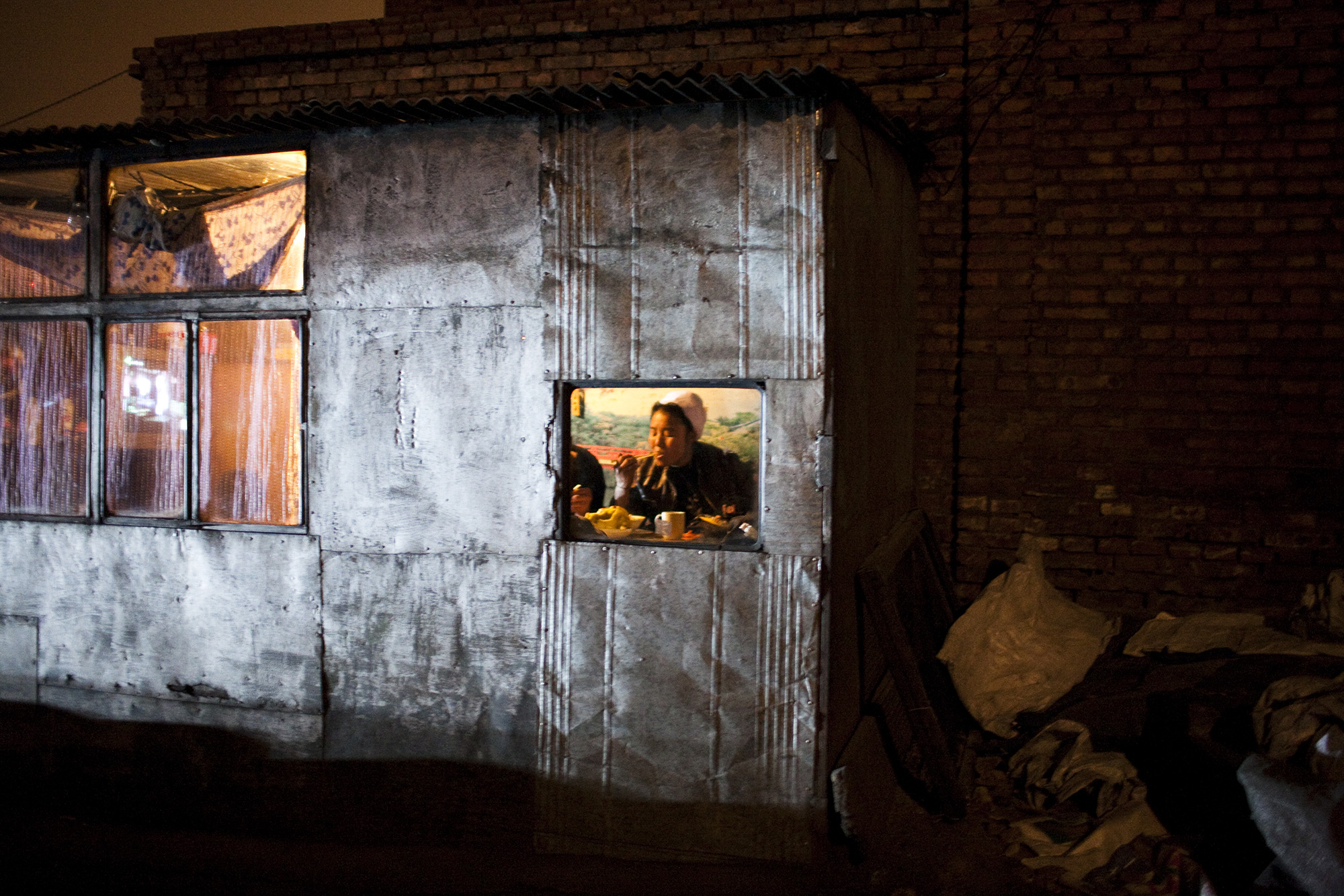 A coal yard boss eats inside her home.