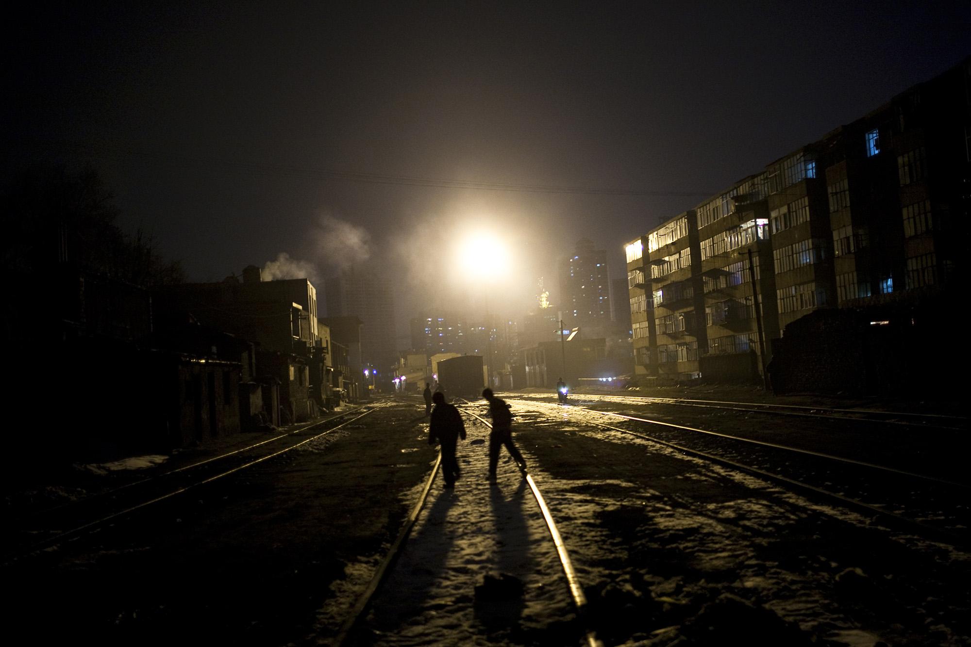 Boys cross the rail tracks.