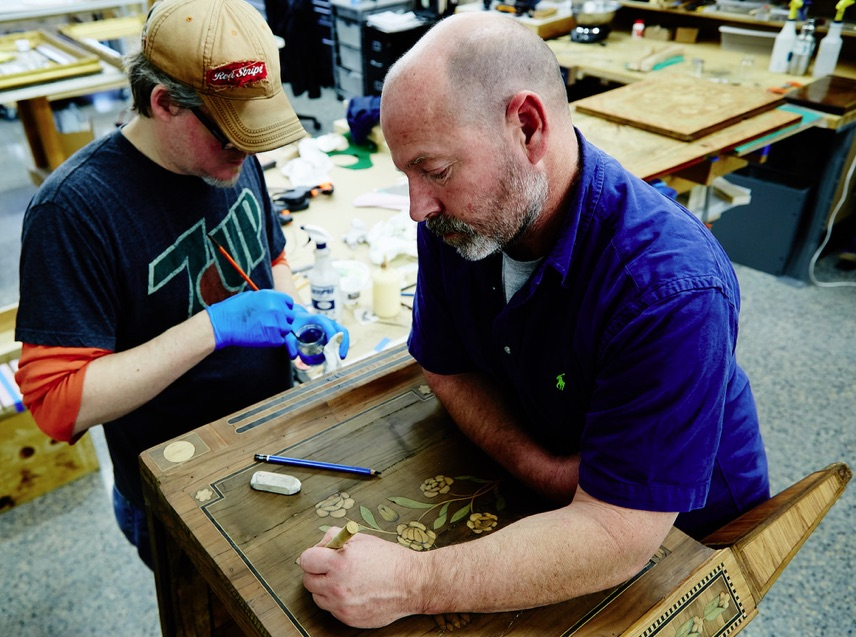Michael Young and Stephen Ryan re-enhancing a leaf motif on a marquetry for a chest of drawers.