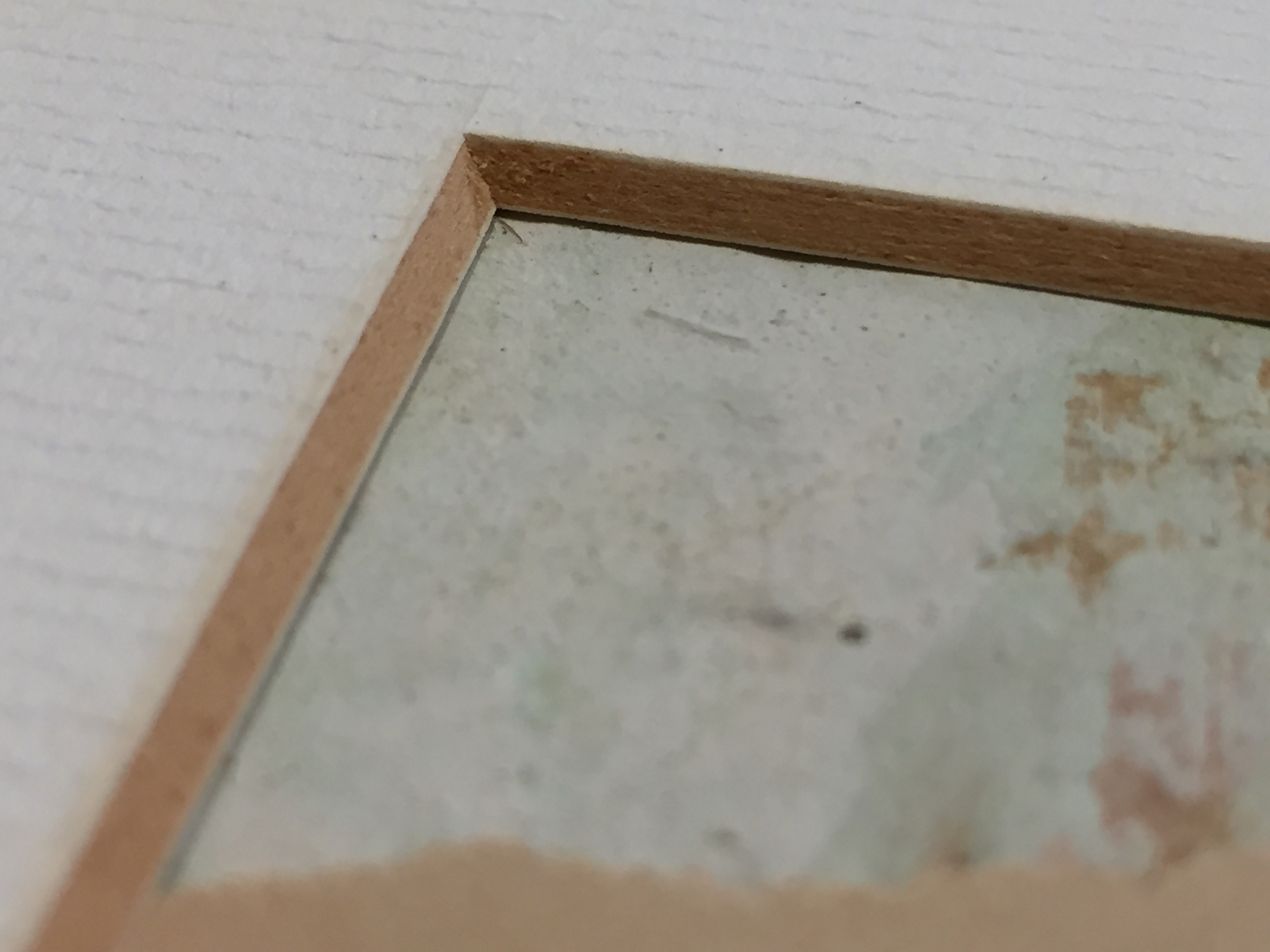 Discoloration in the matboard indicated by the darkened beveled edge is evidence that acid is present.