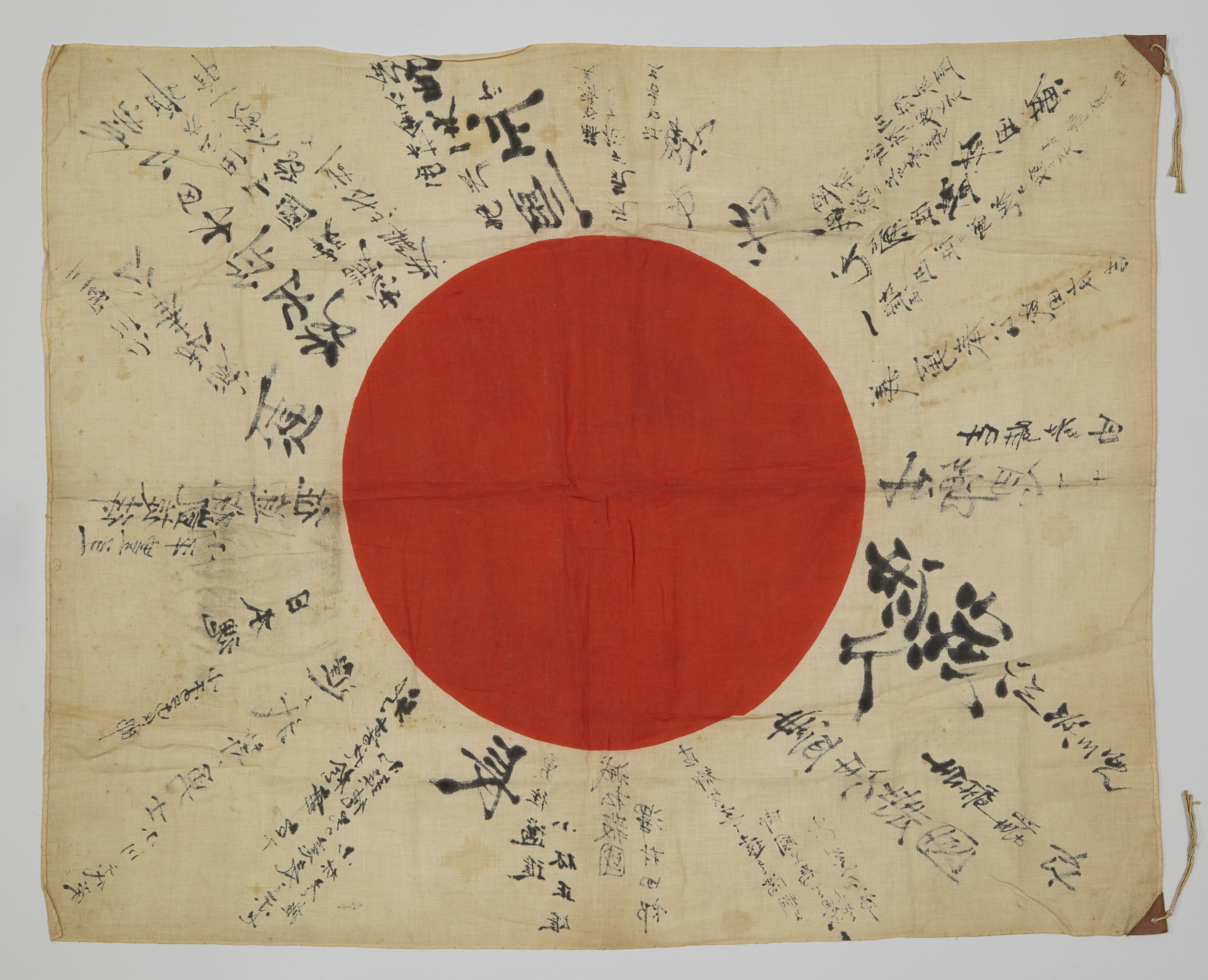 """Before stabilization, this """"good luck"""" flag, or yosegaki hinomaru, shows the history of its age through discoloration of the fibers and heavy creases where it was folded for many years."""