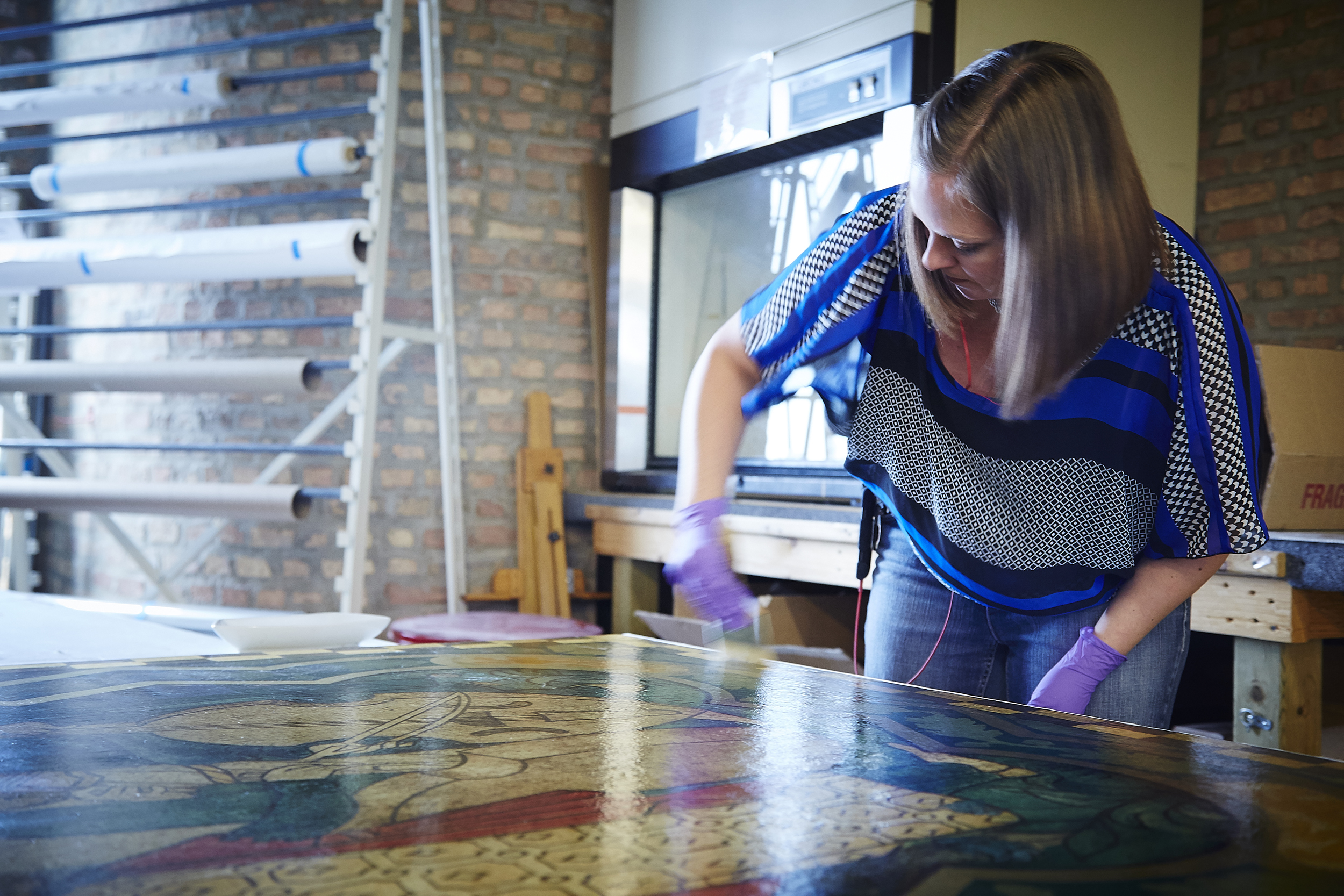 Conservator Amber Schabdach, working on one of the 56 panels that were removed from the Michigan Room ceiling for more extensive treatment back at The Center's Lab.