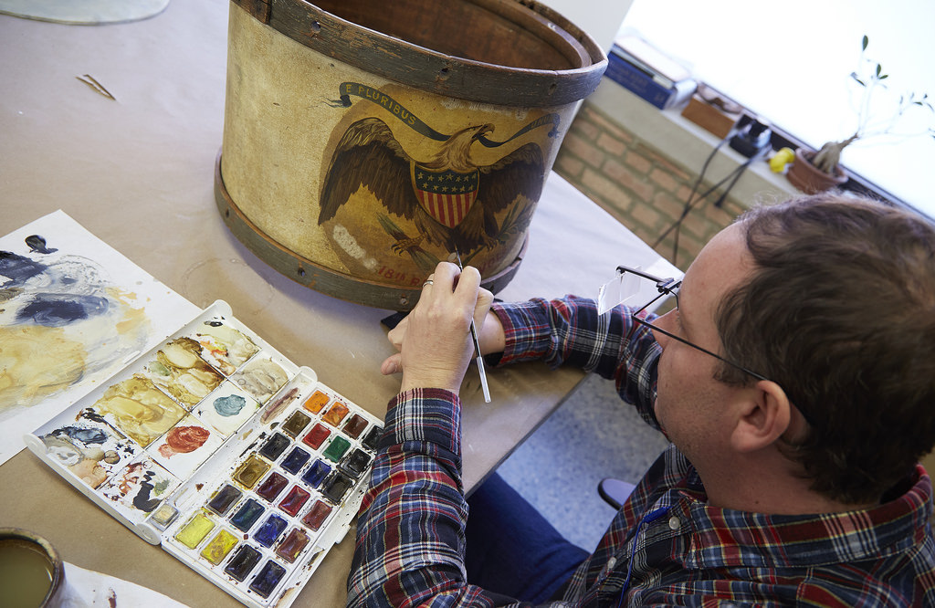 Reversible watercolor and acrylic conservation paints fill areas of loss within the drum.