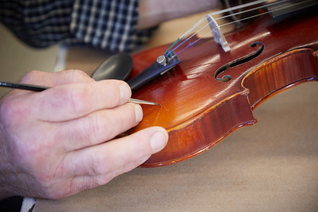 Carefully fixing a scratch on the body of the instrument.