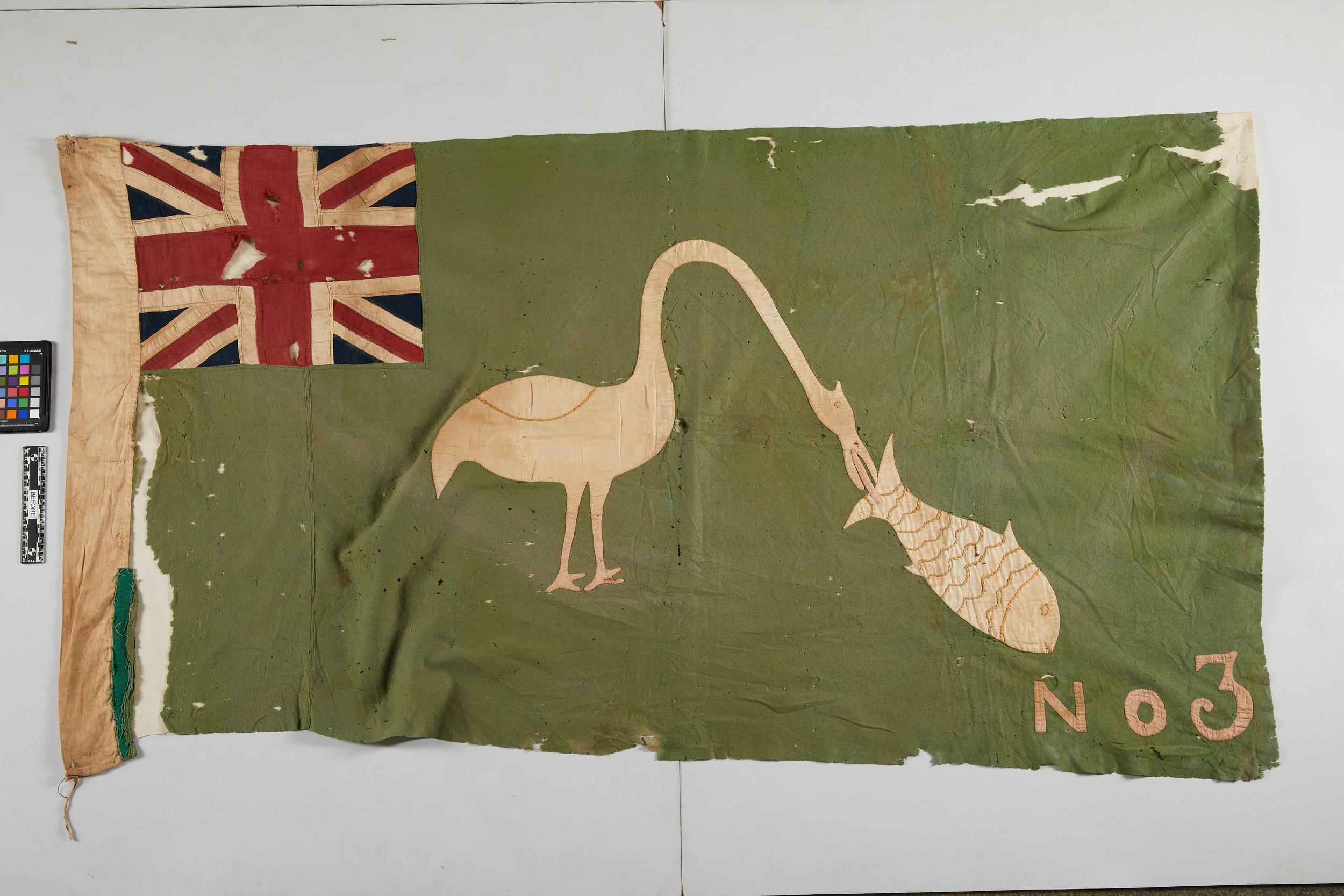 An Asafo flag from the collection with large areas of loss, 36 x 65 inches.