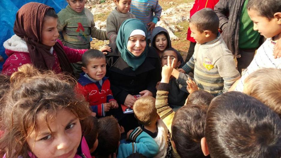 Children crowd around Zein in a camp in southern Aleppo.    Credit:Photo courtsey of Zein.