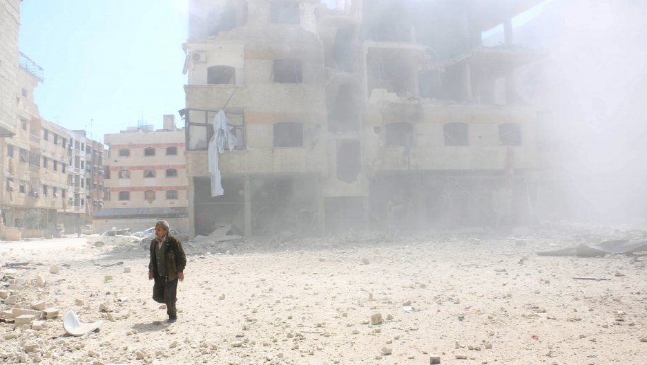 A man walks amid rubble of damaged buildings in Eastern Ghouta, a suburb of Damascus.  Credit:Photo by Amer Almohibany / Reuters.