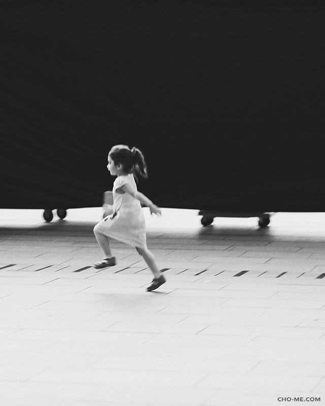 RUNNING ALONG - Feb 21, 2018 - Singapore.Fantasizing her own playground, this little girl had a whale of a time running along that screening black cloth, sometimes her fingers would reach to glide at it, I missed capturing those, this skipping moment save the day