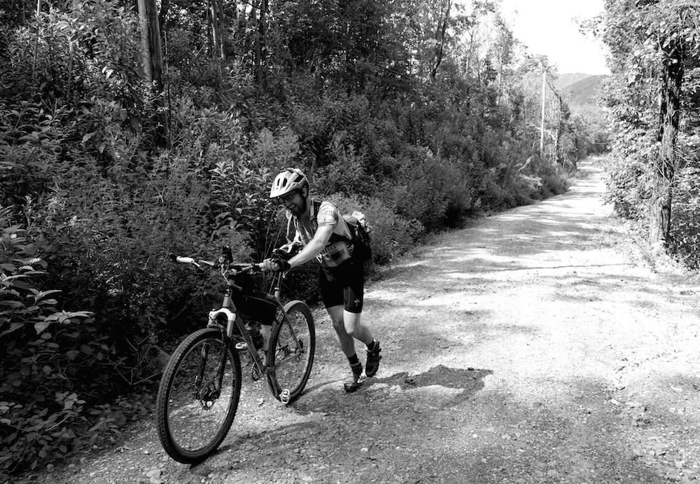 Drew McIntosh pushing up the steep gravel road