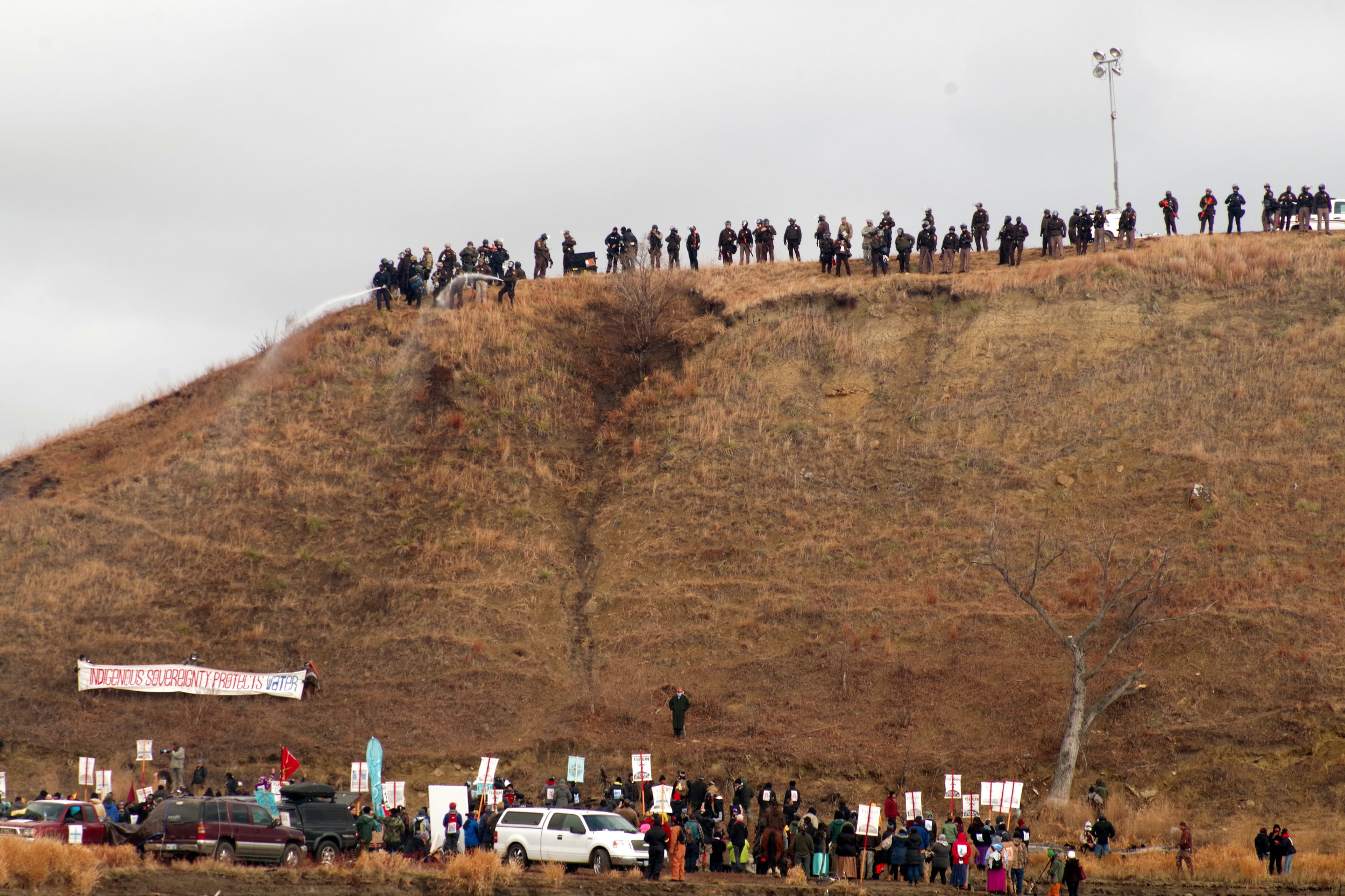 Police standing at the top of Turtle Island with hoses.