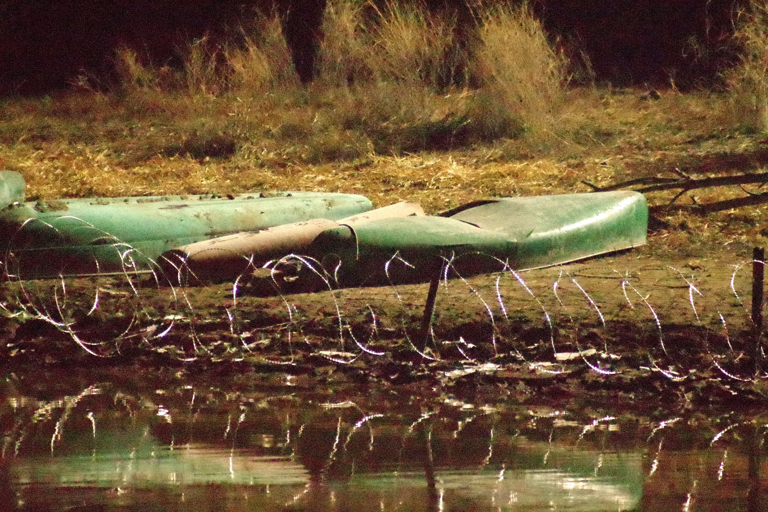 Canoes taken and smashed by cops, and put behind razor wire - at night. Not seen in photo, a beaver swam along the blocked shoreline.