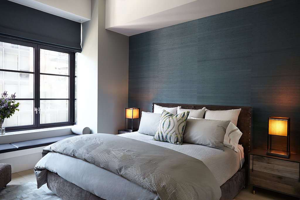 Grasscloth walls , leather headboard hide rug and distressed night stands all mix for  high drama in this relaxing guest room..